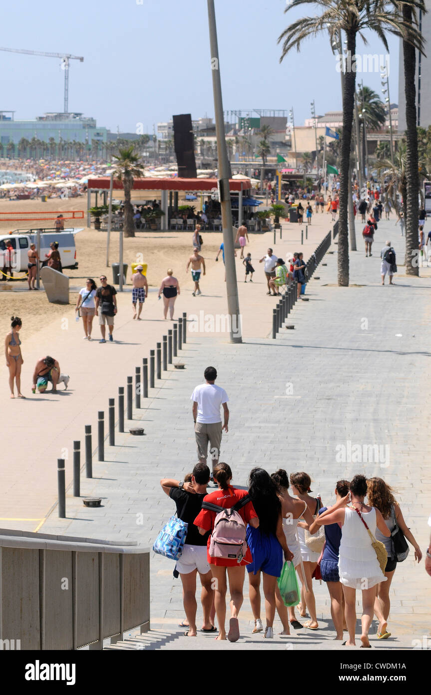 young people going down the stairs right to the seaside,  Barceloneta beach, Barcelona - Stock Image