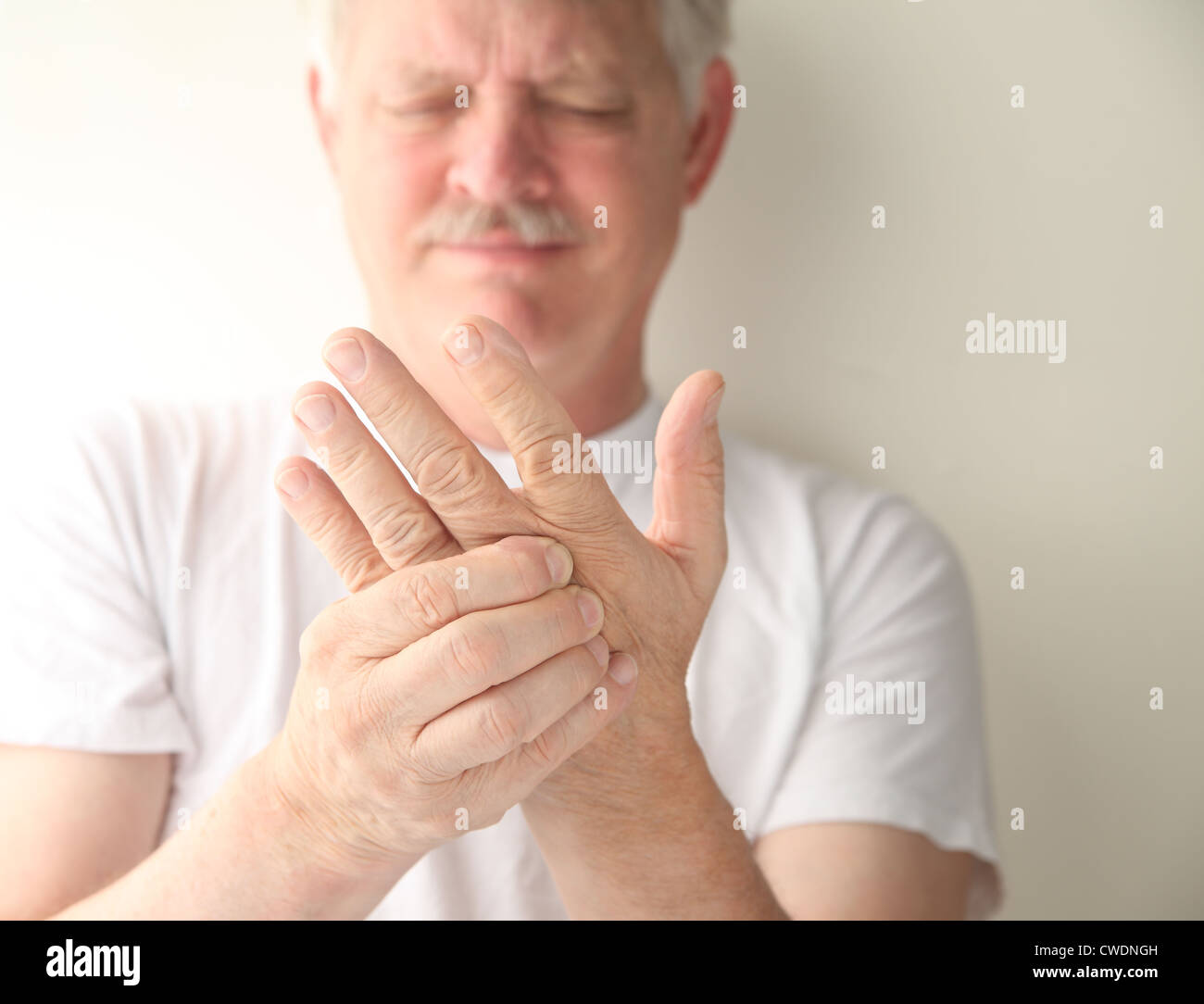 an older man has numbness and tingling in his hand - Stock Image