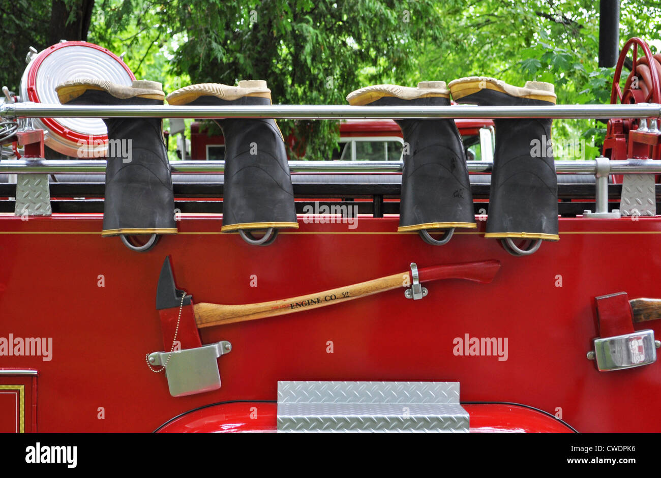 The bright red and chrome of a classic fire engine provide a colorful background for the fire fighter's safety equipment. Stock Photo