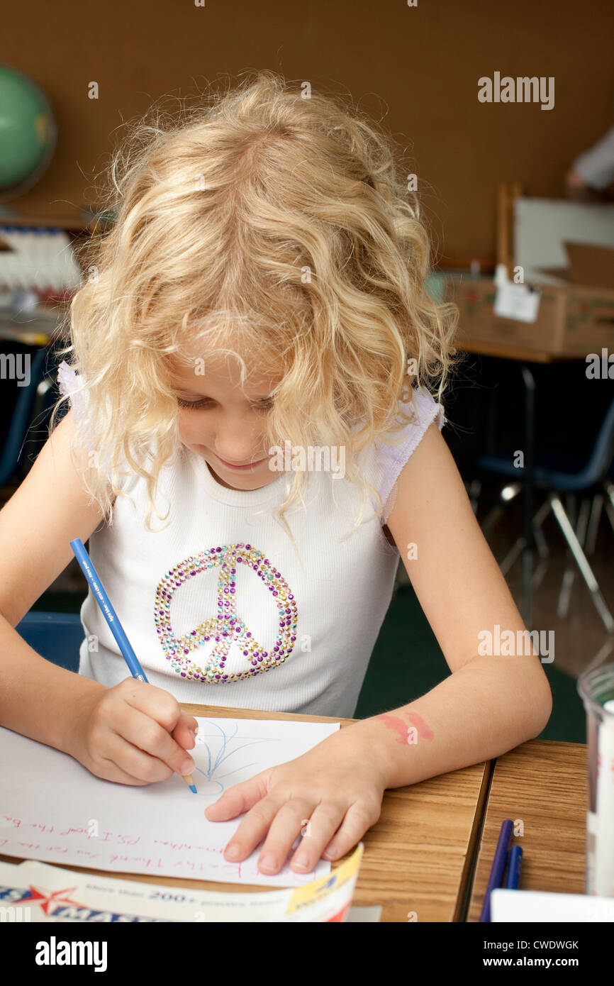 7 Year old blond white girl uses colored pencil to draw on white paper at desk - Stock Image