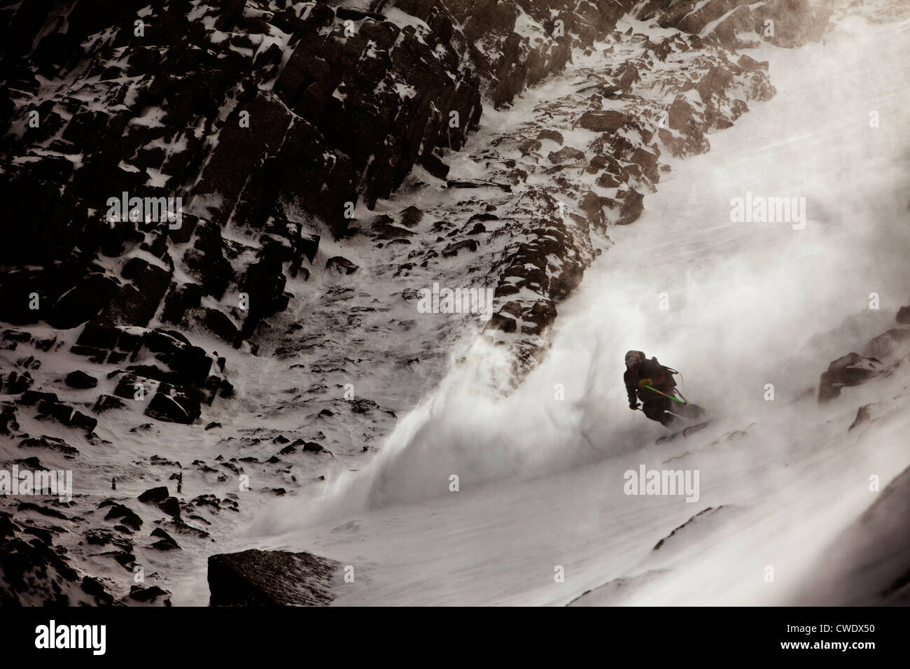 A athletic skier charges down a rocky mountain in the back country in Montana. - Stock Image