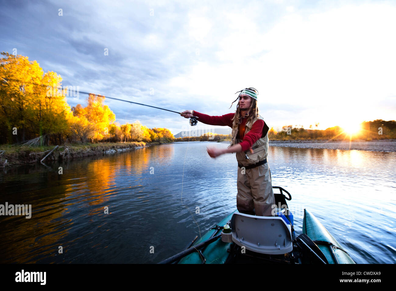 A fly fisher casting his line out of a boat while fly fishing surrounded by fall colors in Montana. - Stock Image