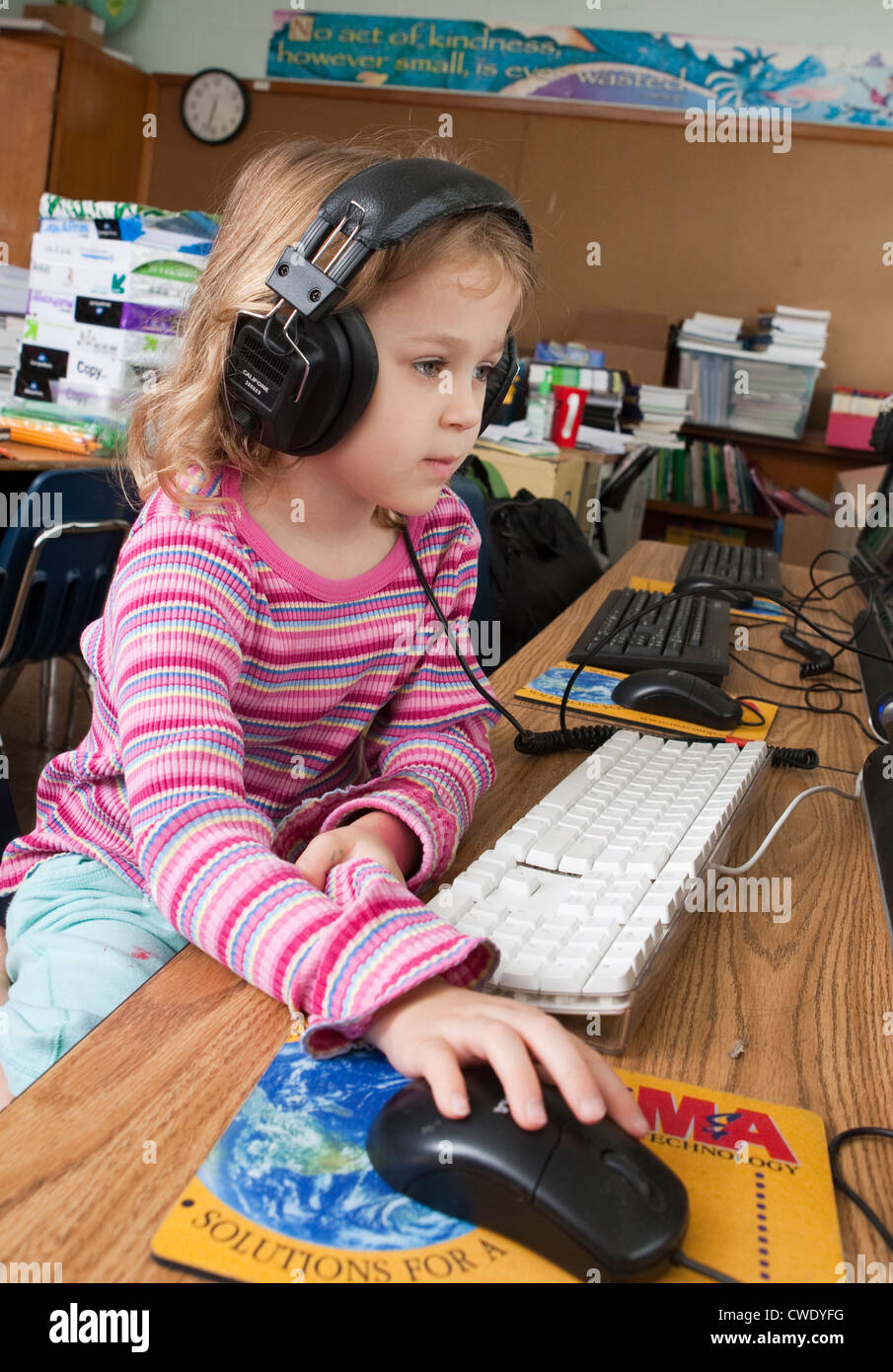 Young 6 year old white girl uses headphones and computer mouse to use educational computer games in classroom - Stock Image