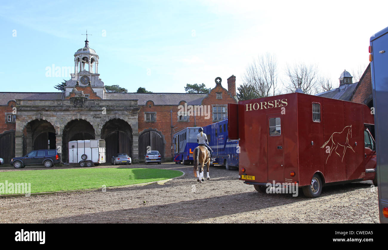 A young woman riding a horse and Horse boxes at Ingestre Hall Stables Ingestre near to Stafford Staffordshire England - Stock Image