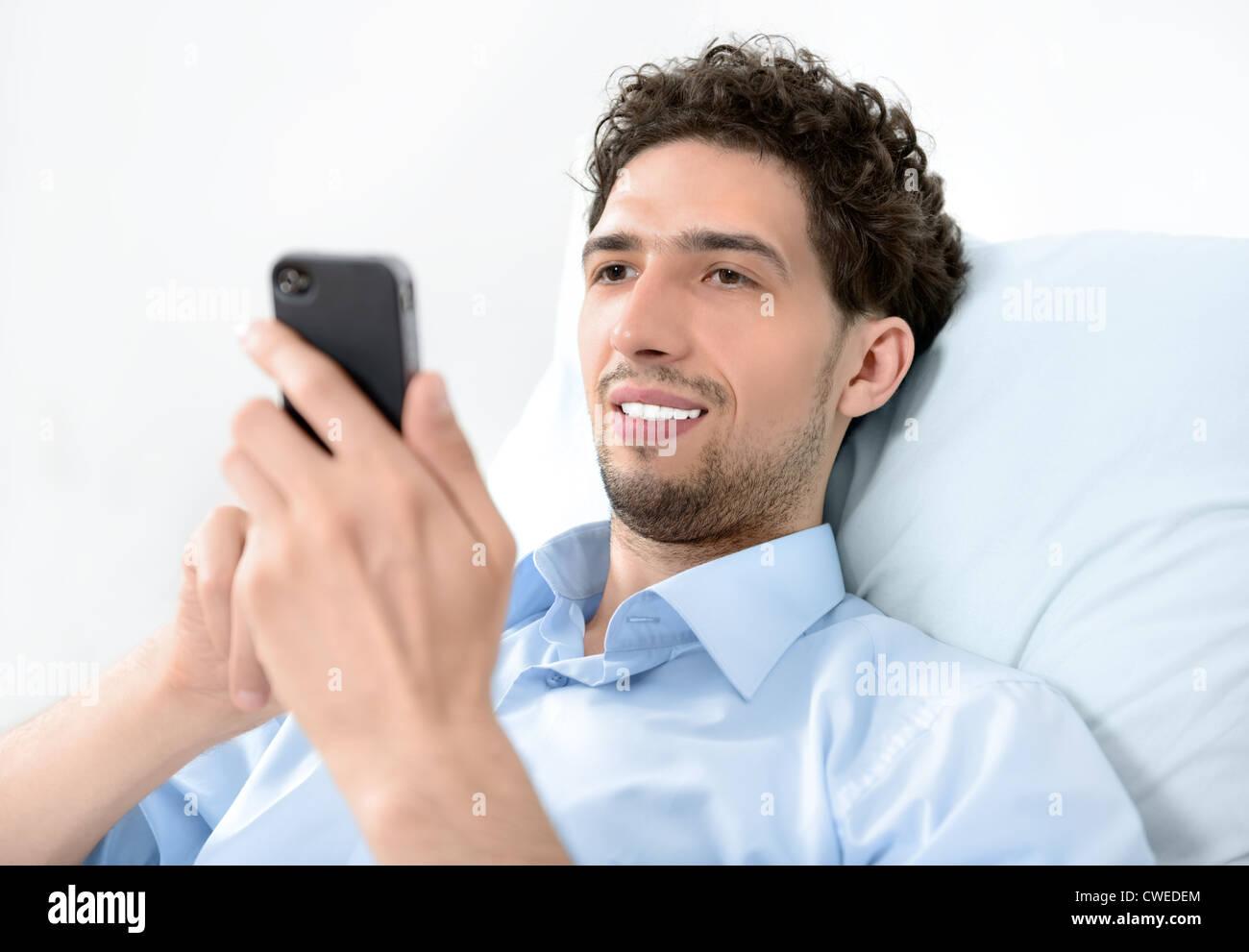 Young handsome man using modern mobile smart phone. Studio shot. - Stock Image