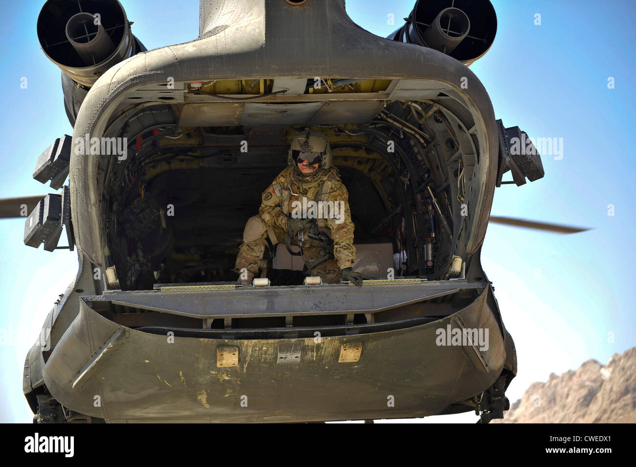 A crew member aboard a CH-47 Chinook helicopter relays information to the pilot as the aircraft approaches a remote - Stock Image