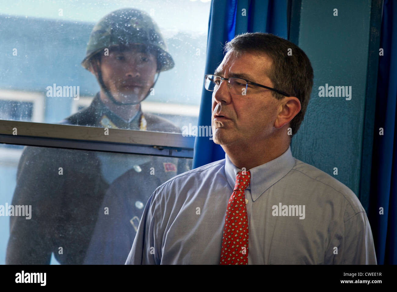 Under the watchful eye of a North Korean soldier, Deputy Secretary of Defense Ashton Carter tours the Military Armistice - Stock Image
