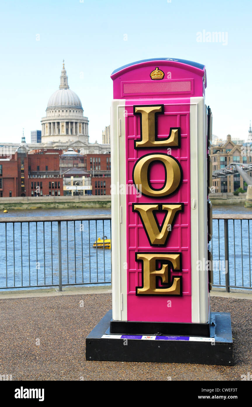 Love Phone Box with St Paul's Cathedral in the background on The Southbank, London - Stock Image