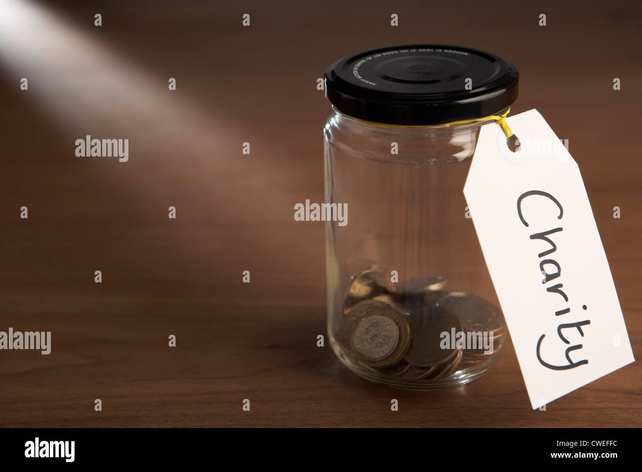 Coins in a jam jar - Stock Image