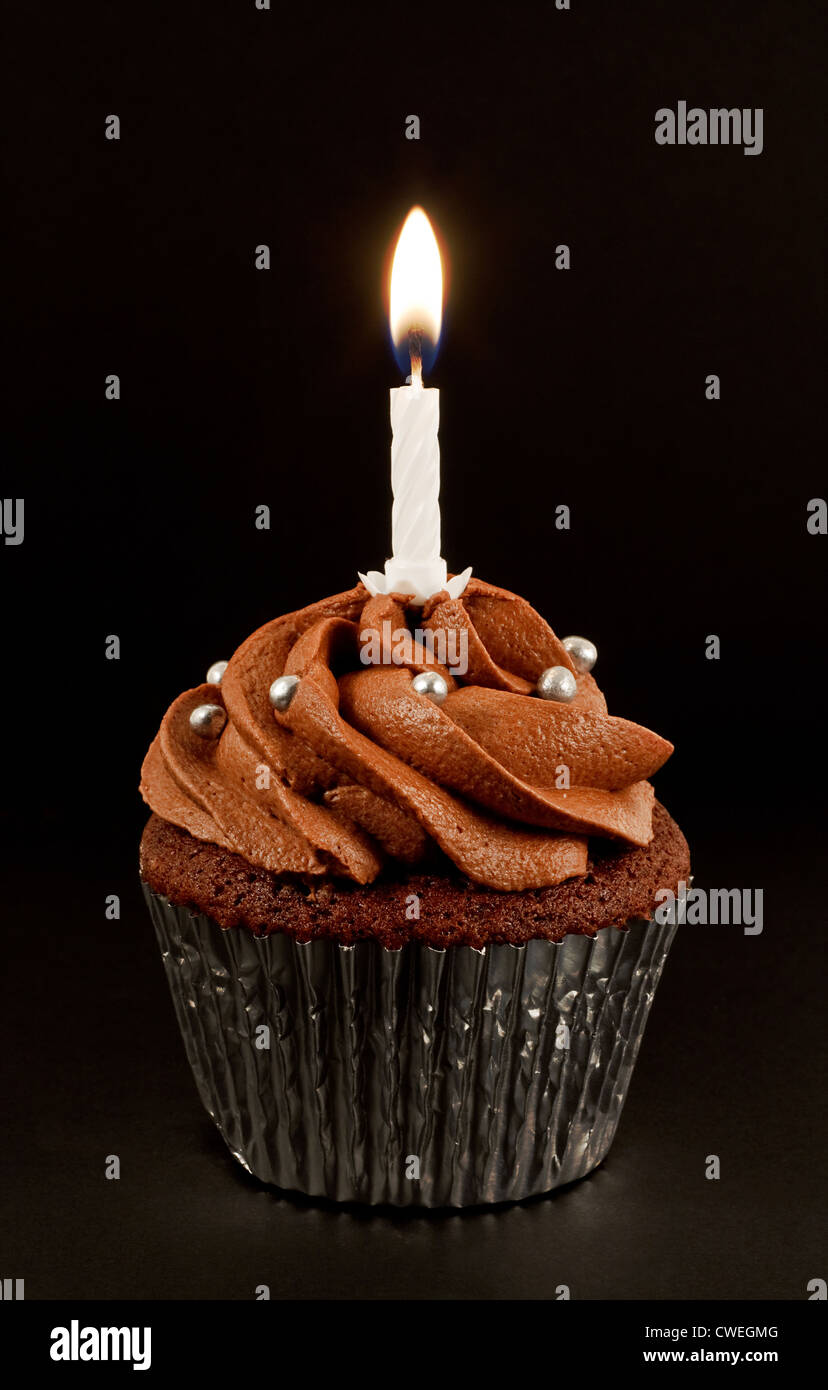 A home baked chocolate cup cake with a single lit candle to ...