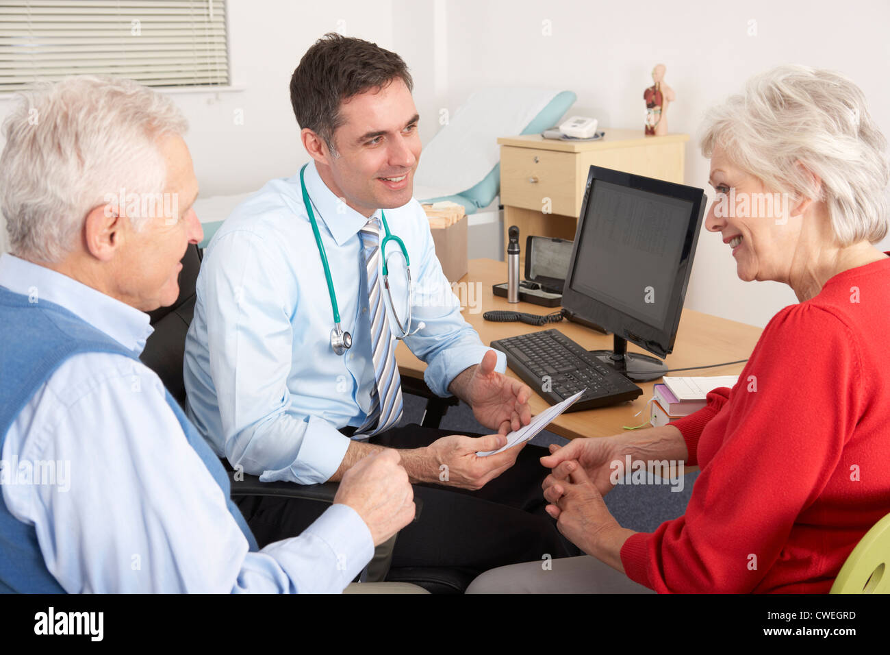 British GP talking to senior couple in surgery Stock Photo