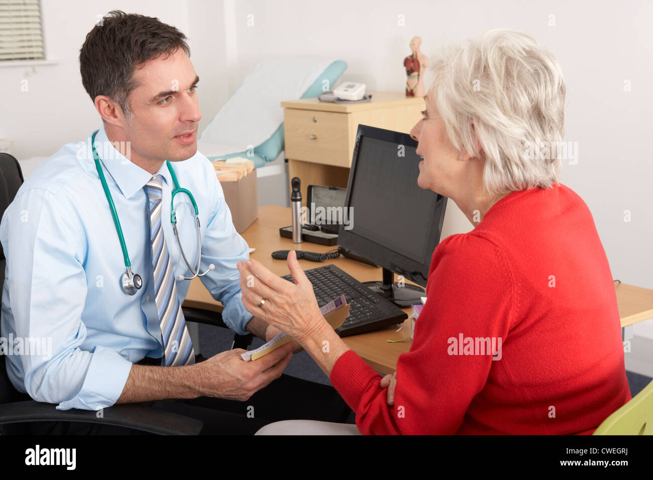 British GP talking to senior woman in surgery - Stock Image