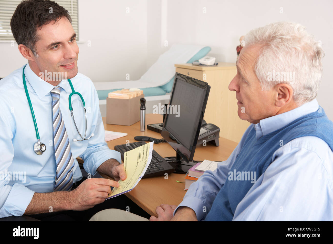 British GP talking to senior man in surgery - Stock Image