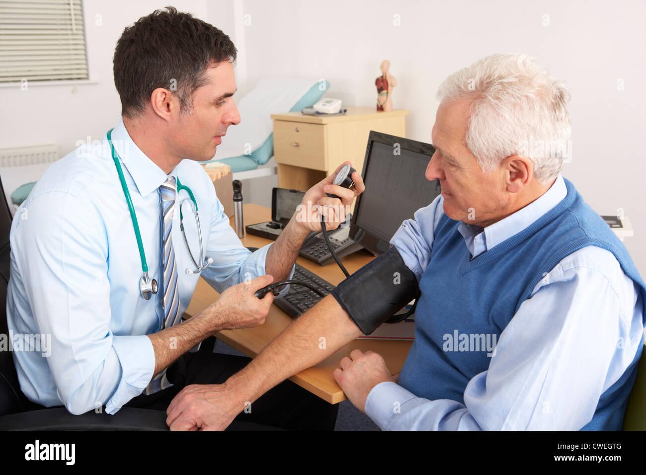 British doctor taking senior man's blood pressure - Stock Image