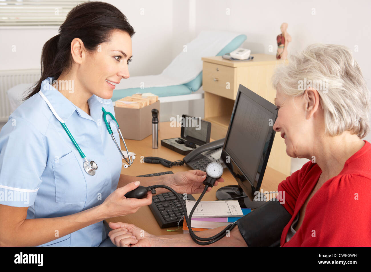 British nurse taking senior woman's blood pressure - Stock Image