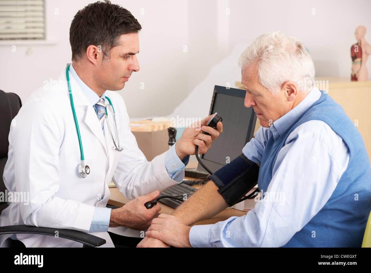 American doctor taking senior man's blood pressure - Stock Image