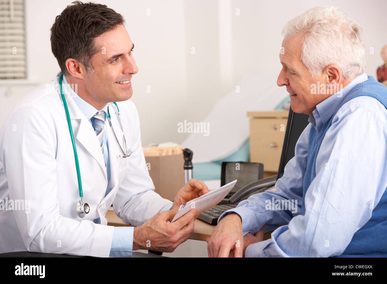American doctor talking to senior man in surgery - Stock Image