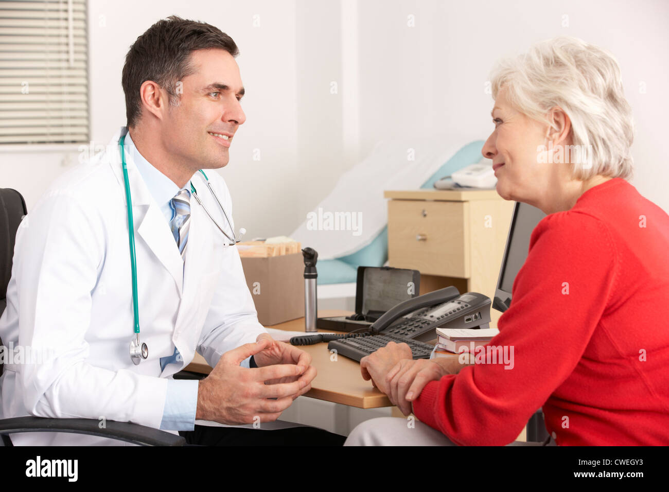 American doctor talking to senior woman in surgery - Stock Image