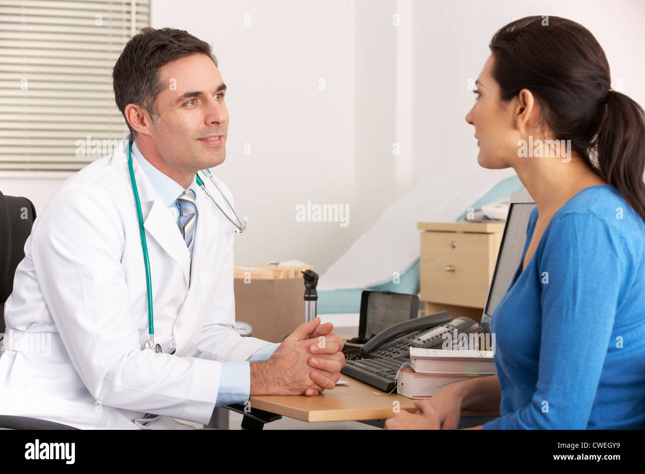 American doctor talking to woman in surgery - Stock Image