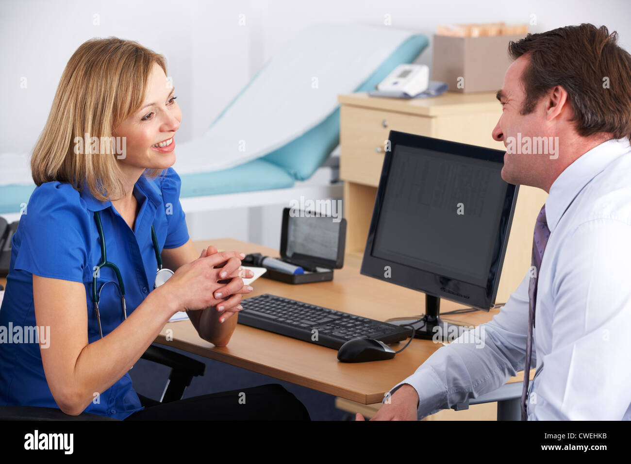 Female UK doctor talking to male patient - Stock Image