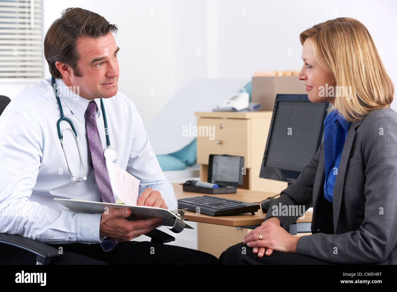 American doctor talking to businesswoman patient - Stock Image