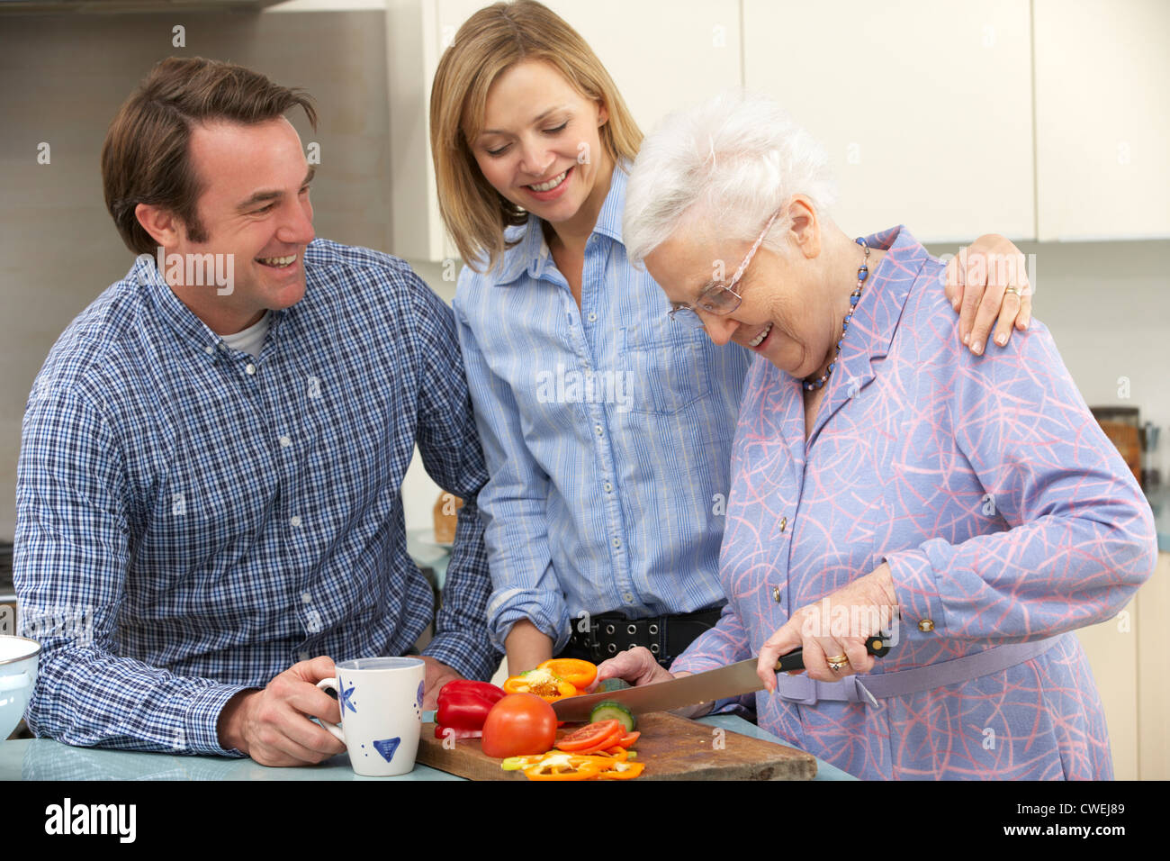 Senior woman and family preparing meal together - Stock Image