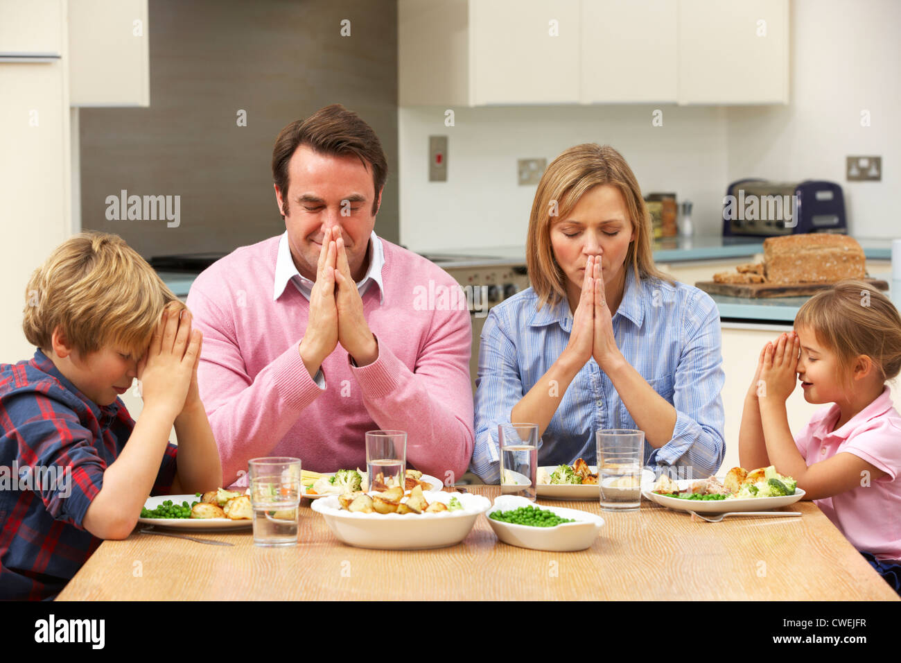 Family saying grace before meal - Stock Image