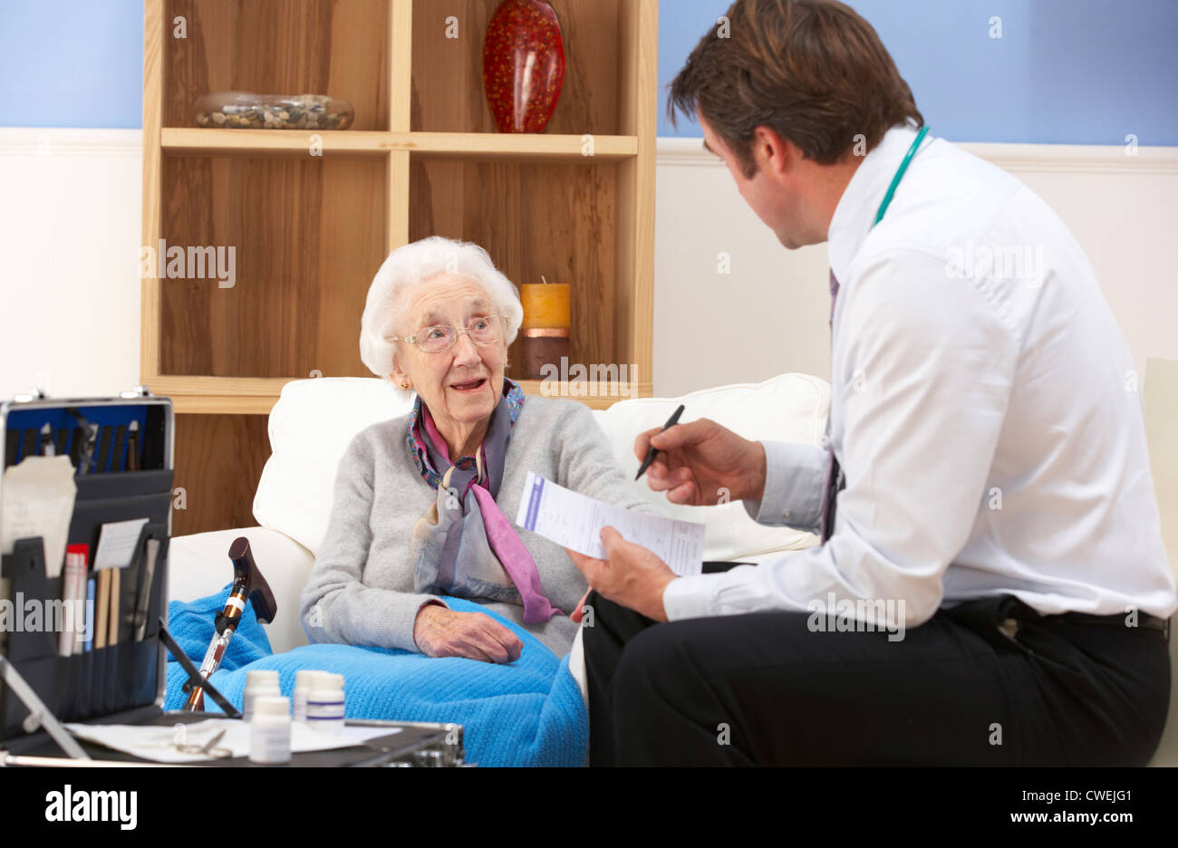 UK GP visiting senior woman at home - Stock Image