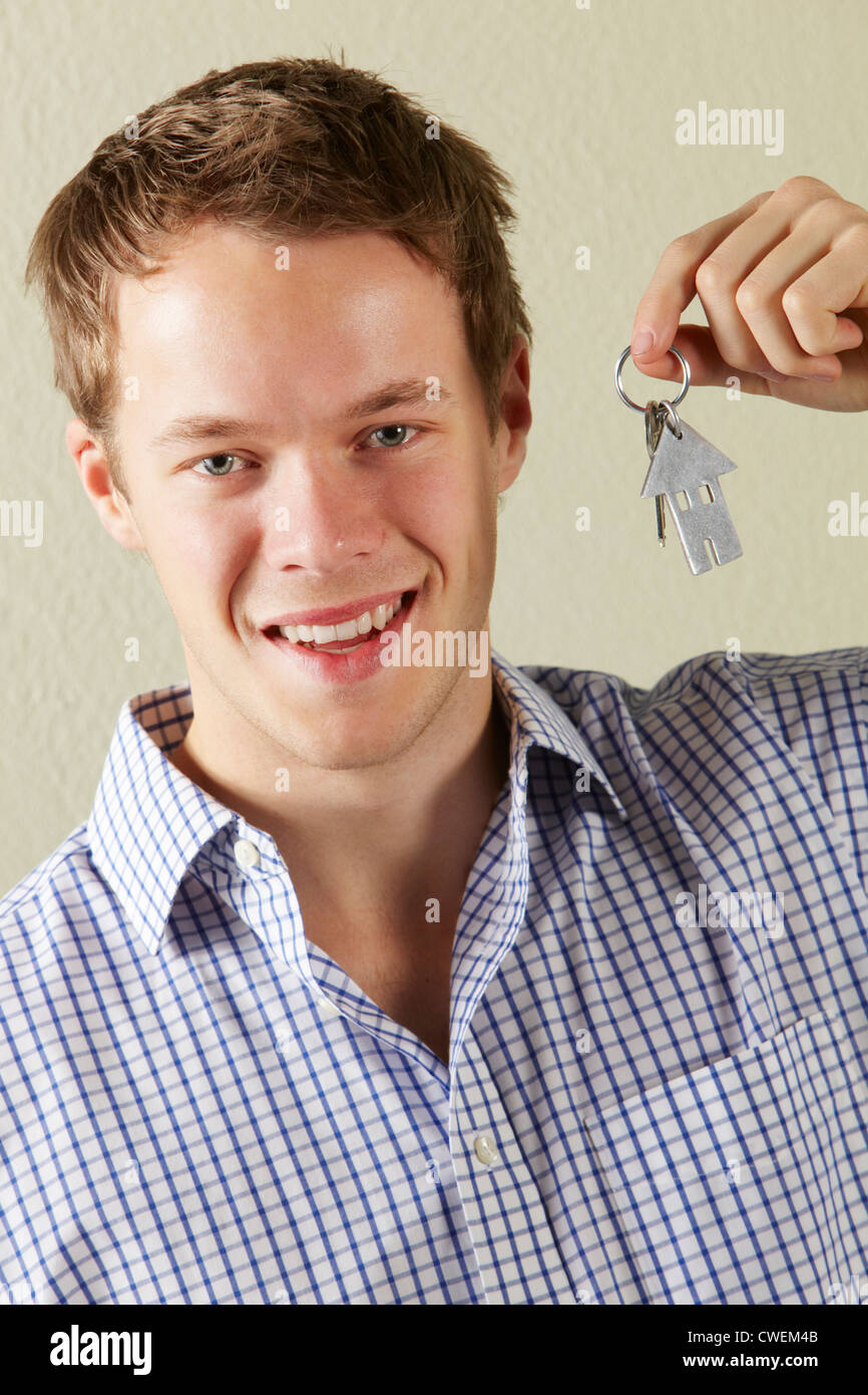 Studio Shot Of Young Man Holding Keys To First Home - Stock Image