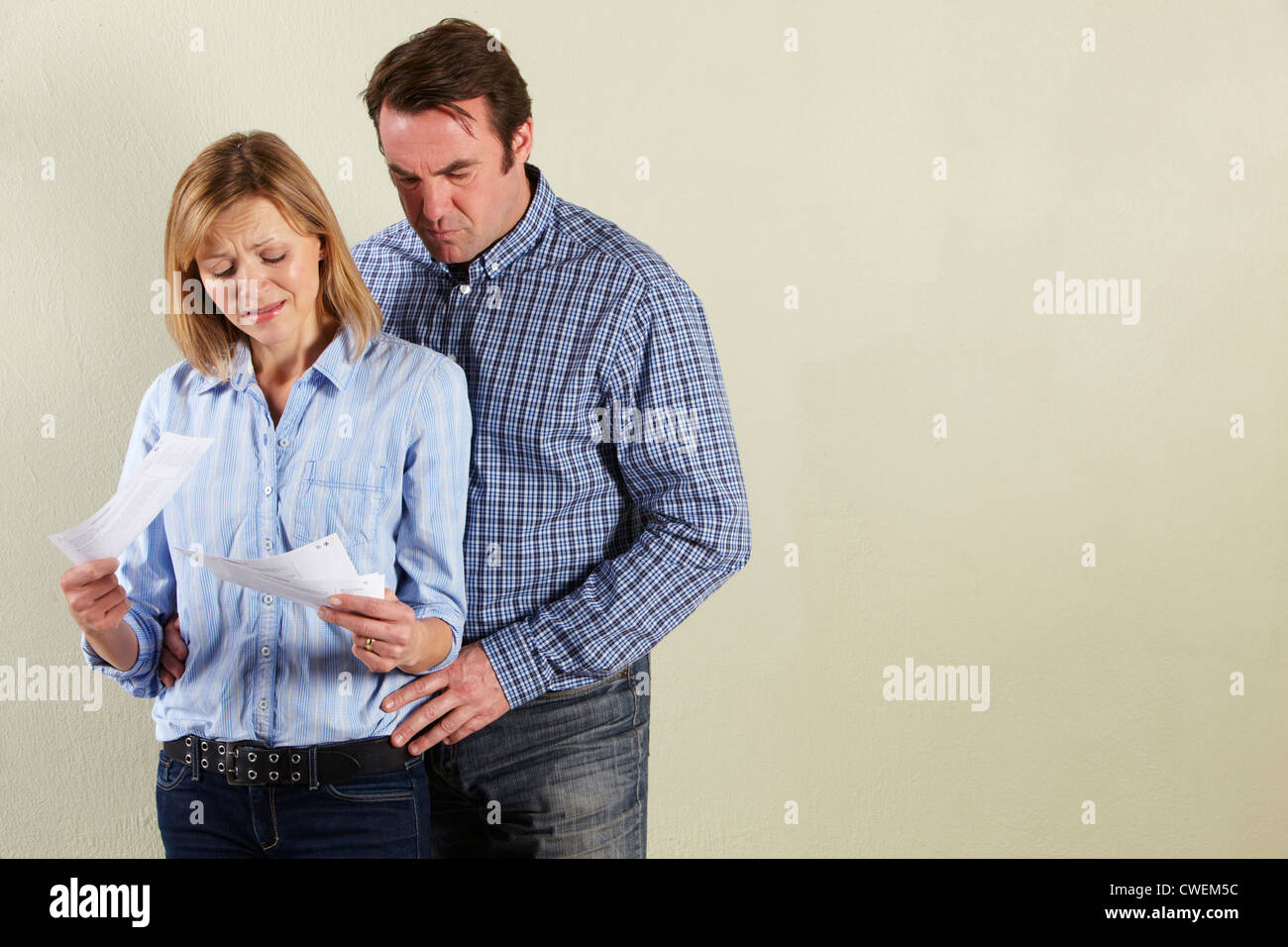 Studio Shot Of Middle Aged Couple Looking at Bills - Stock Image