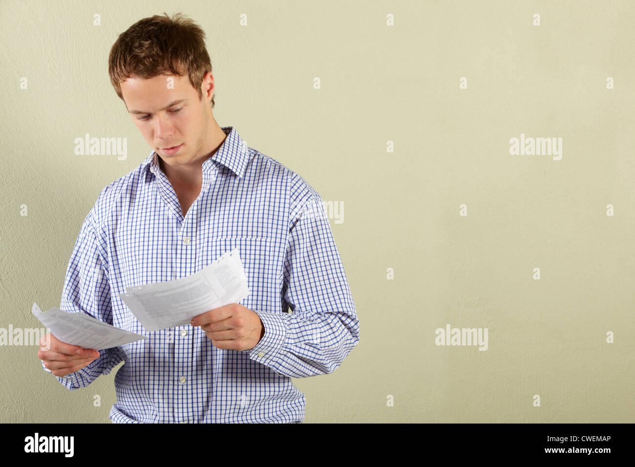 Studio Shot Of Young Man Looking at Bills - Stock Image