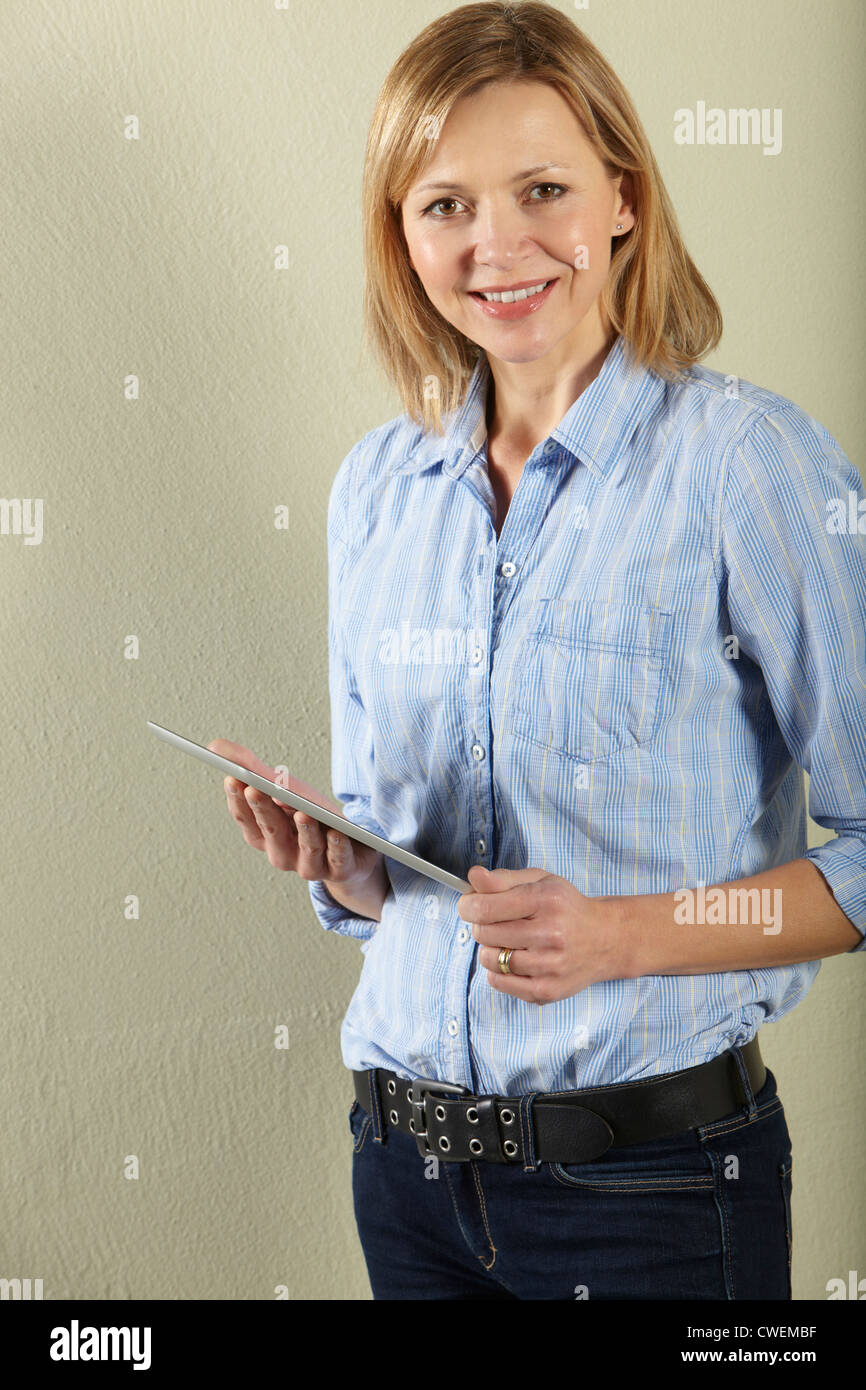 Studio Shot Of Middle Aged Woman Using Tablet Computer - Stock Image