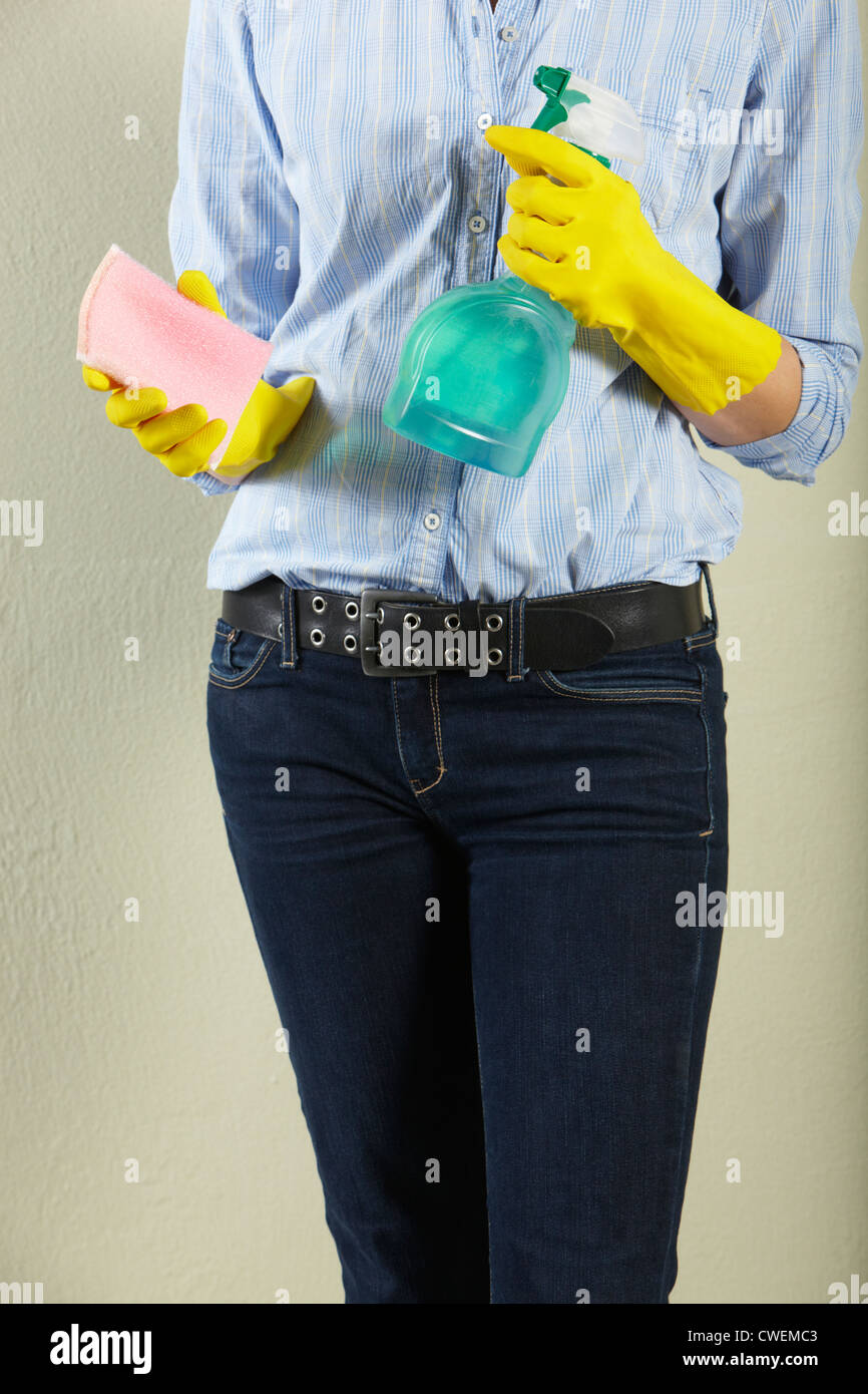 Cropped Shot Of Middle Aged Woman Holding Cleaning Products - Stock Image