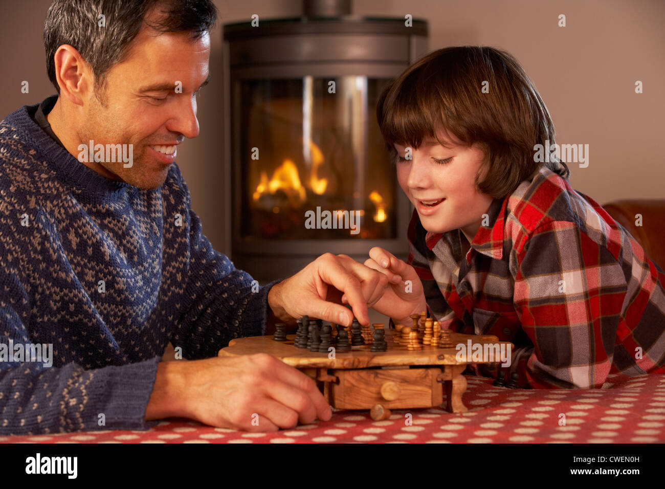 Father And Son Playing Chess By Cosy Log Fire - Stock Image