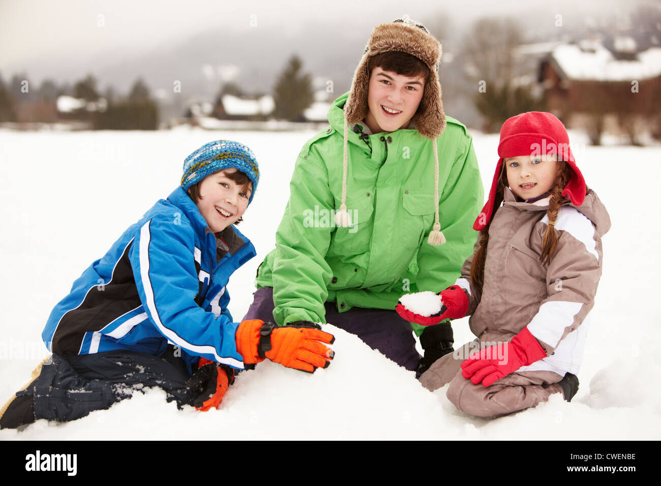 Group Of Children Building Snowman Wearing Woolly Hats - Stock Image