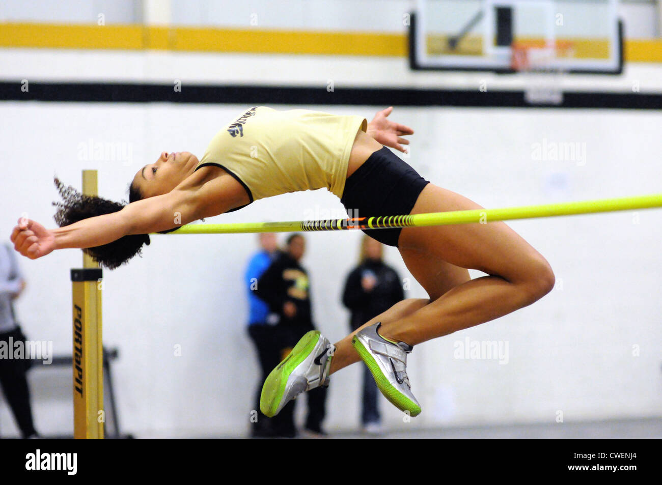 High Jump Female athlete clears the bar on a high jump pass during a high school indoor track meet. USA. - Stock Image