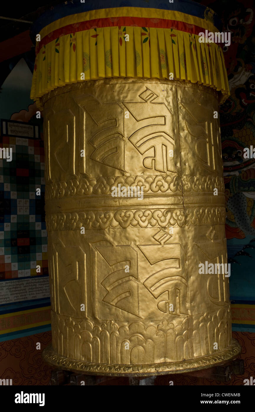 A giant bronze prayer wheel in the the magnificent Punakha Dzong in Bhutan is constantly being turned by its many - Stock Image