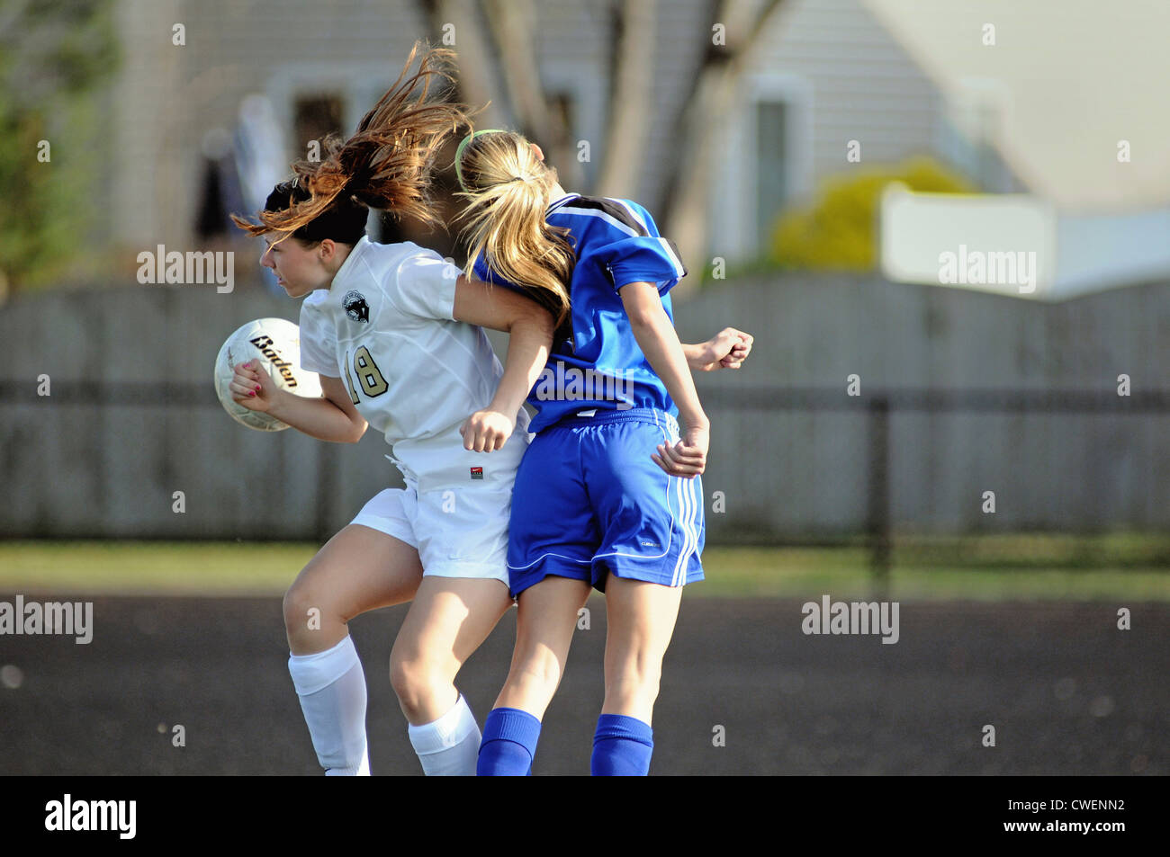 Soccer players battle for possession of the ball along the goal line during a high school match. - Stock Image