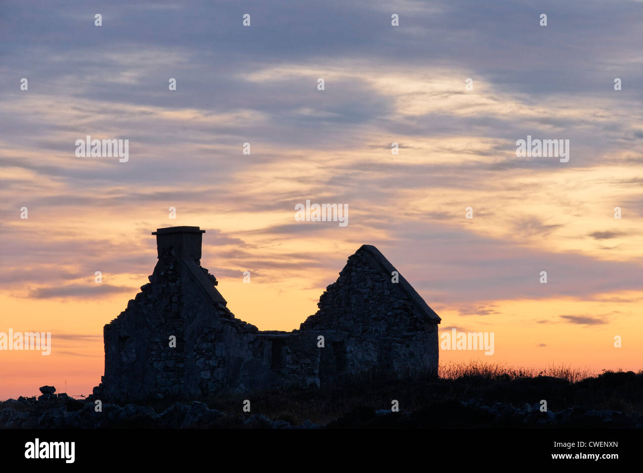 Ruined cottage silhouetted against sunset sky. Near Beal an Daingin, Connemara, County Galway, Connaught, Ireland. - Stock Image