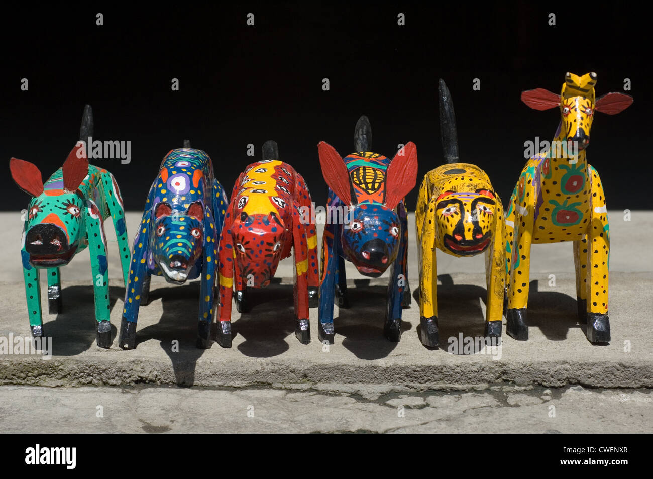Highly colourful but primitive carved wooden toy animals on sale in the street in Santiago Atitlan, Guatemala. - Stock Image