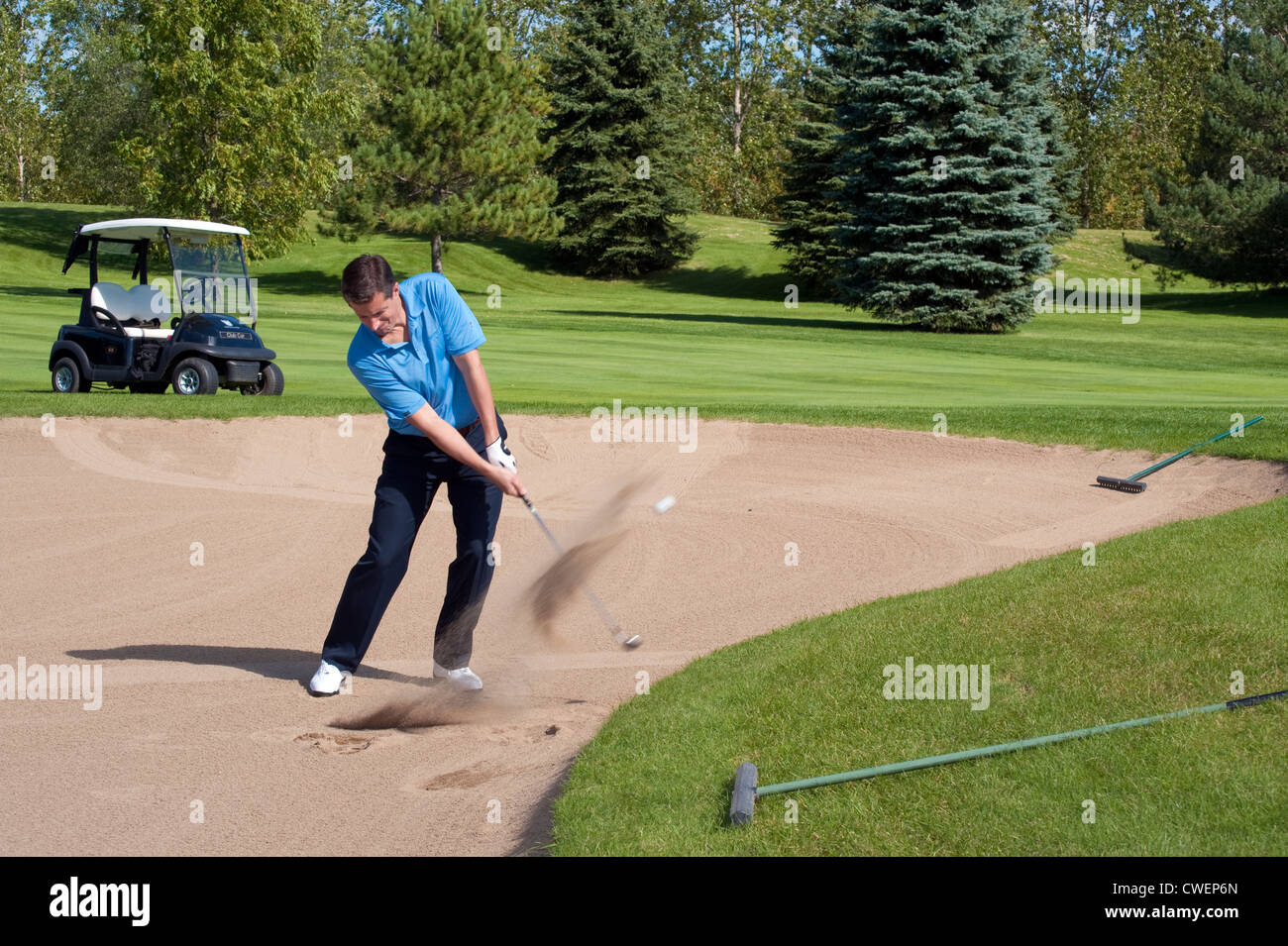 Golfer blasting out of sand trap. - Stock Image