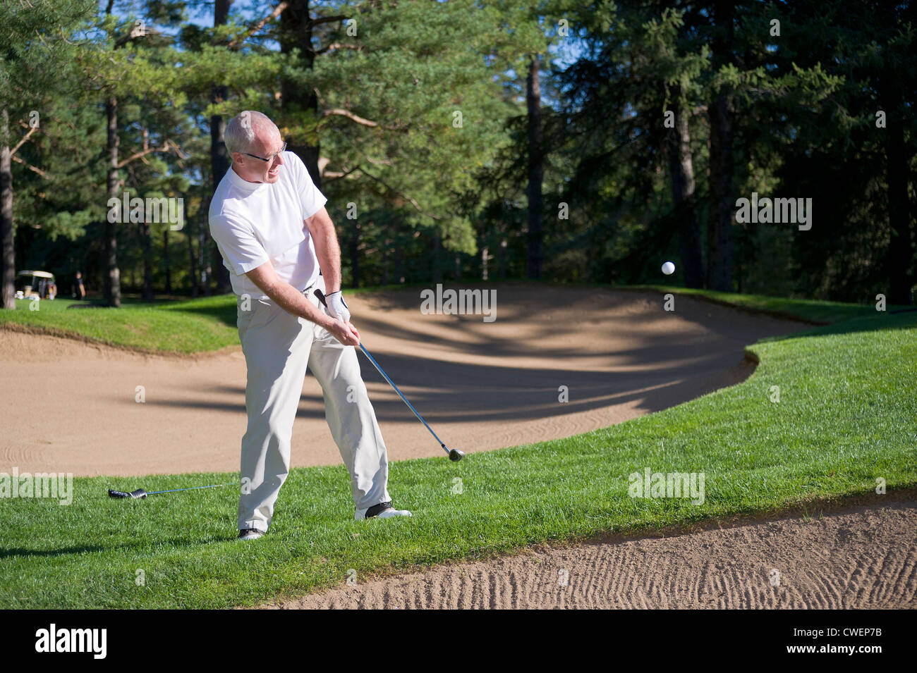 Golfer chipping his ball onto the green. - Stock Image