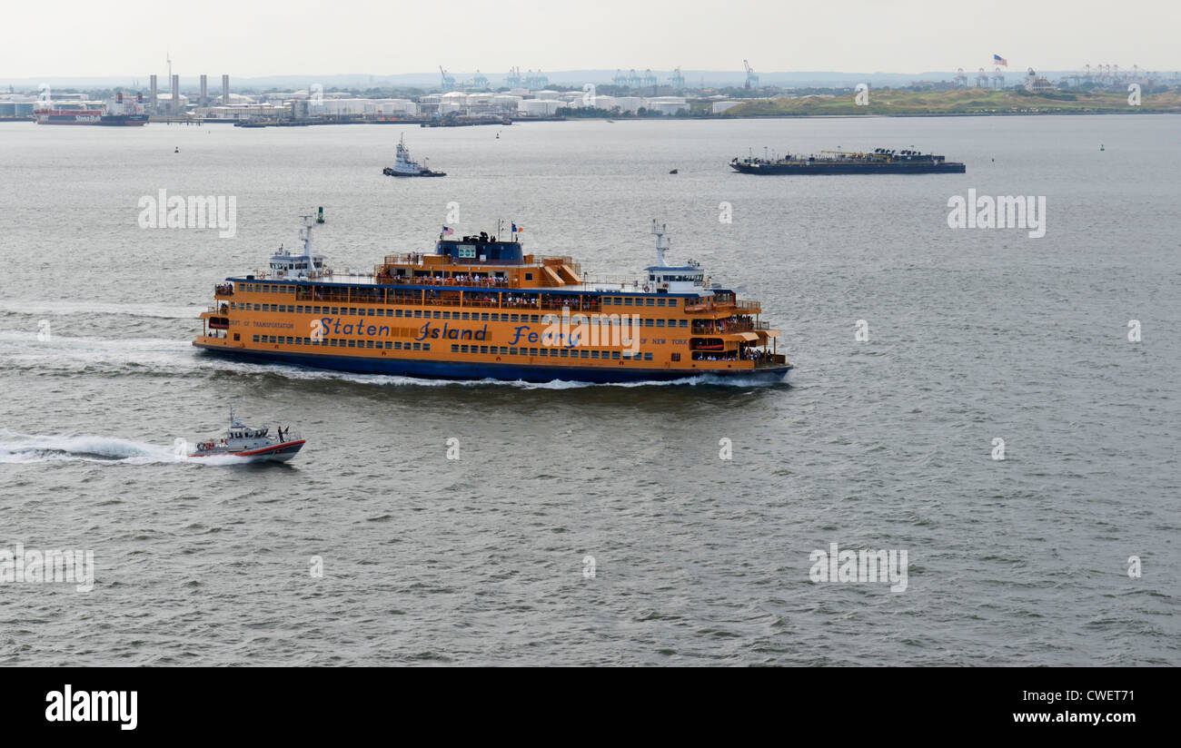 Staten Island Ferry in New York Harbor with armed Coast Guard escort - Stock Image