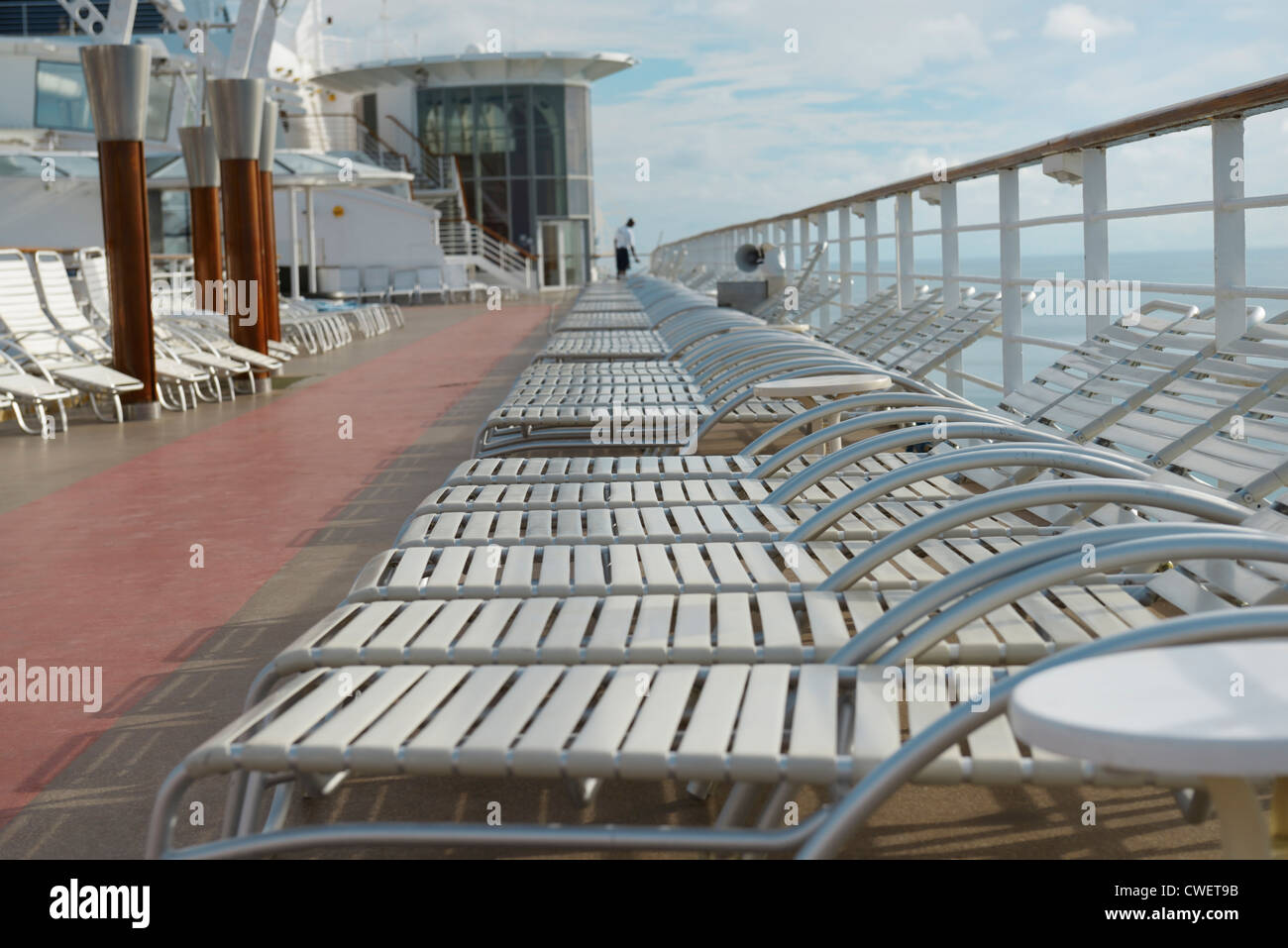 Empty cruise ship deck chairs with deckhand cleaning, early morning at sea - Stock Image