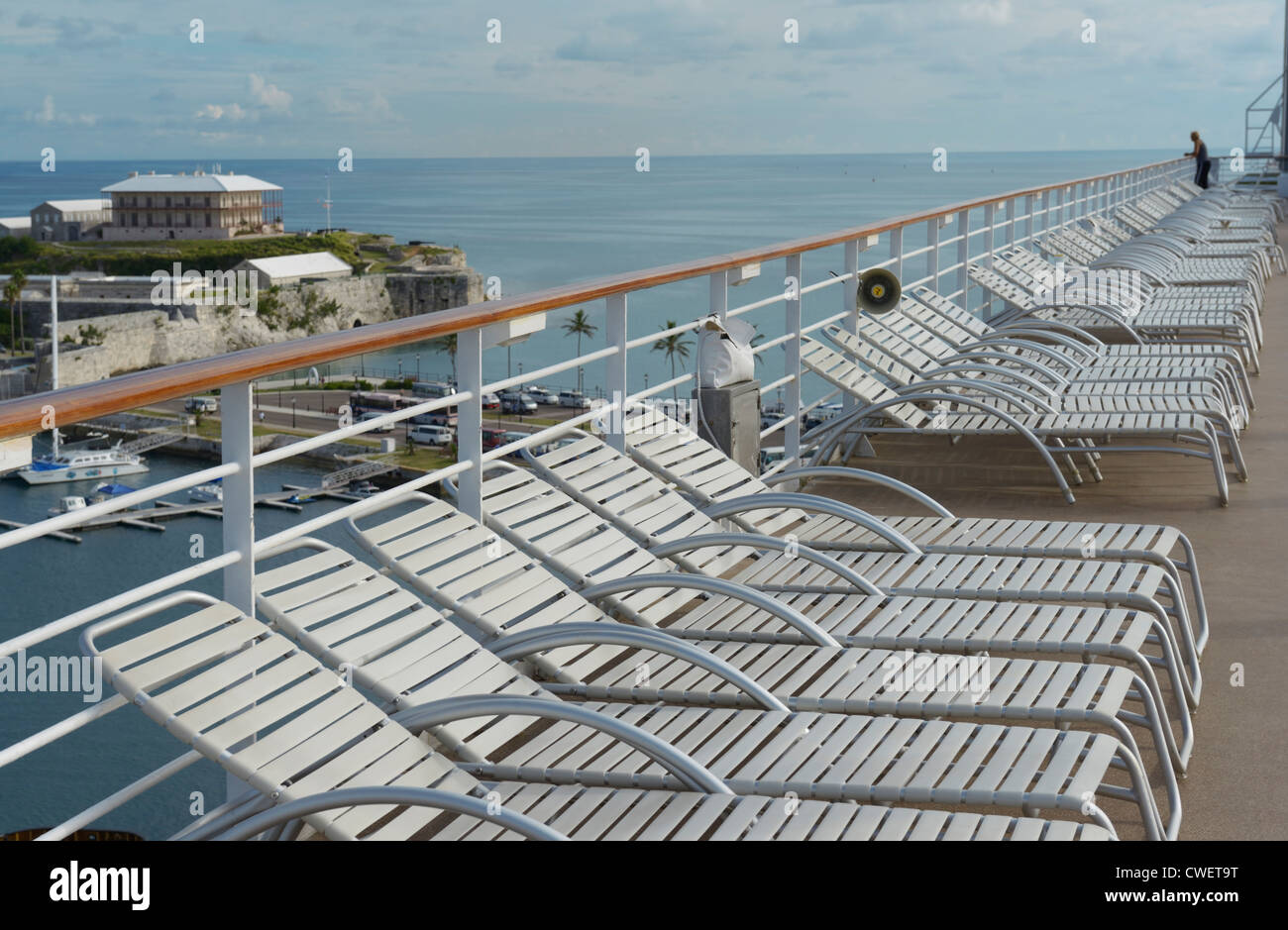Empty cruise ship deck chairs, King's Wharf Bermuda, The Commissioner's House in view - Stock Image