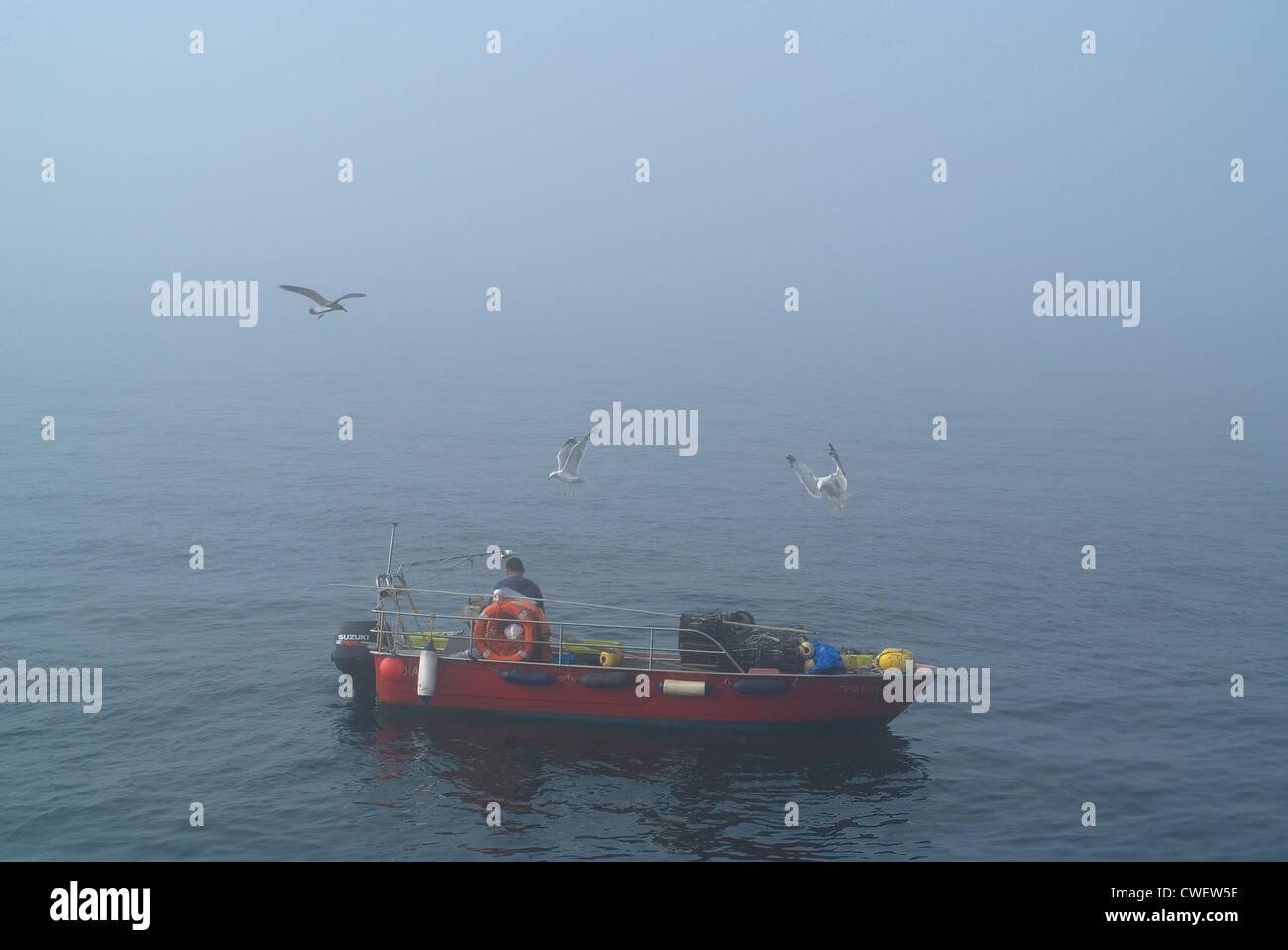 Artisan fisherman working in the mist - Stock Image