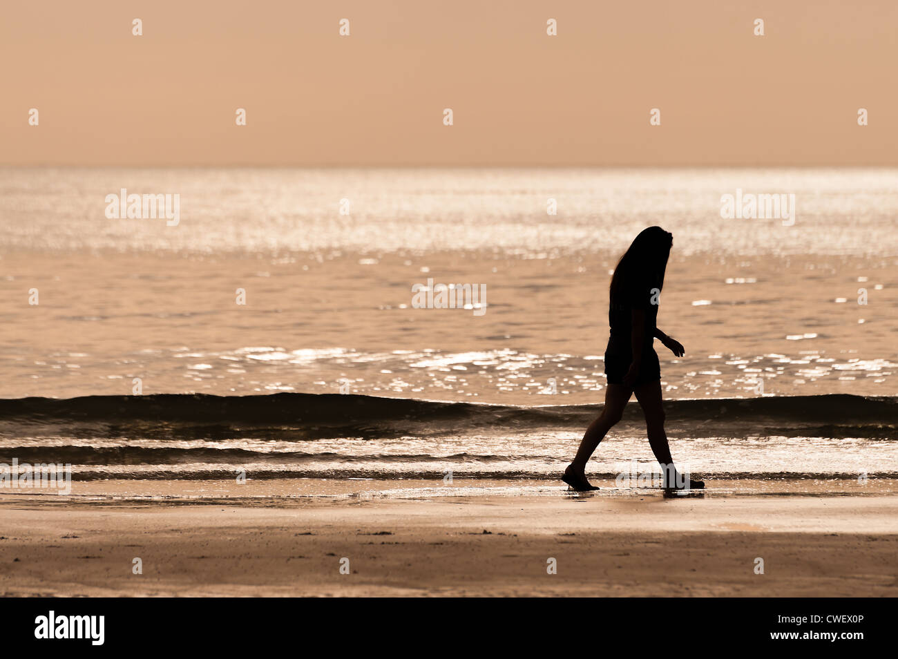 sillhouette woman walking on the beach - Stock Image