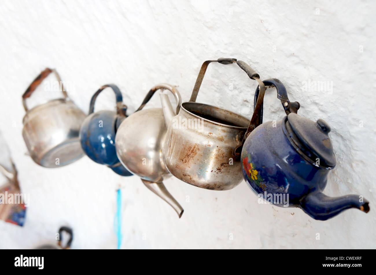 Old metallic teapots fixed hanging on a white wall - Stock Image