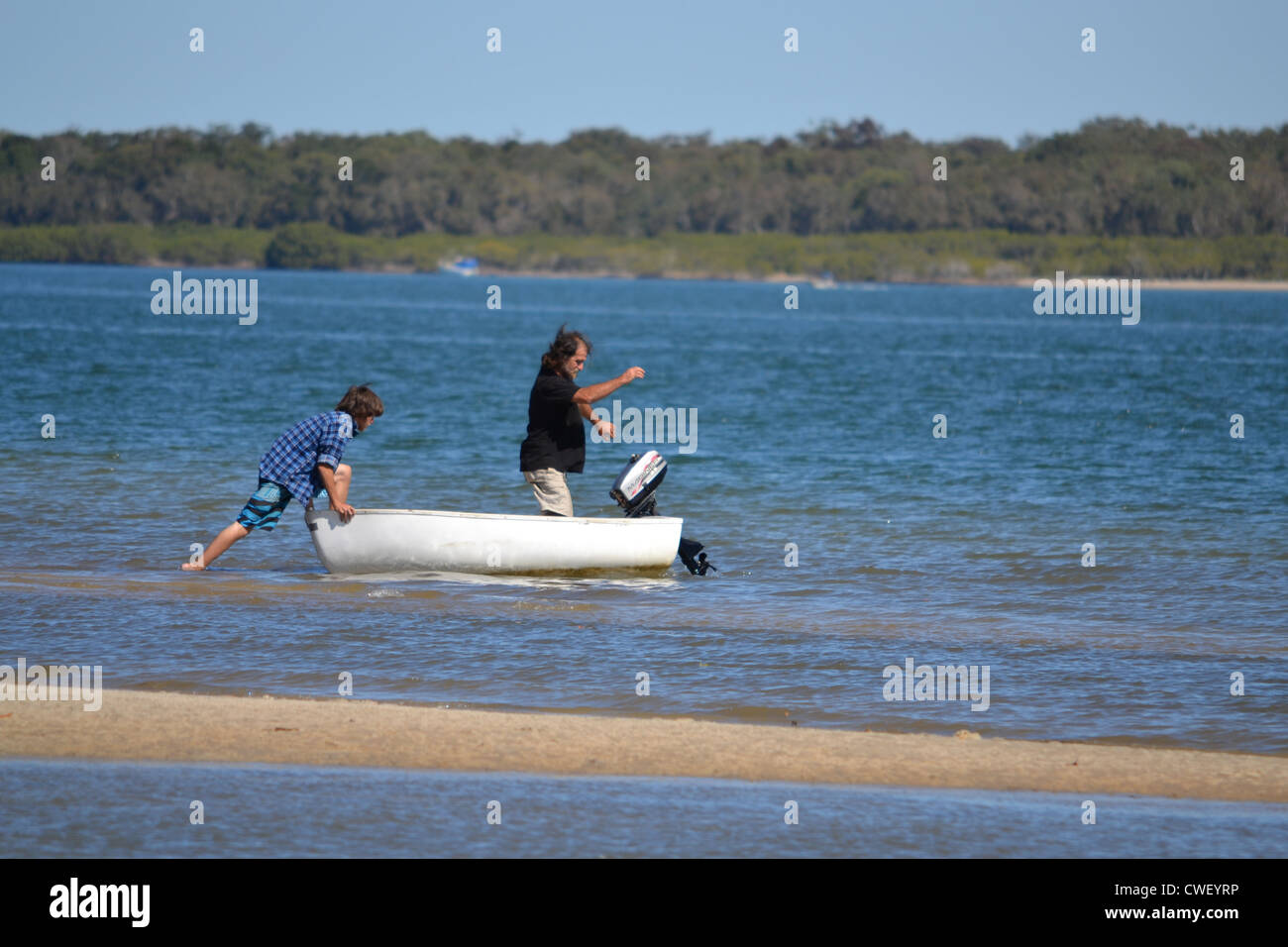 father and son go for ride in small boat - Stock Image