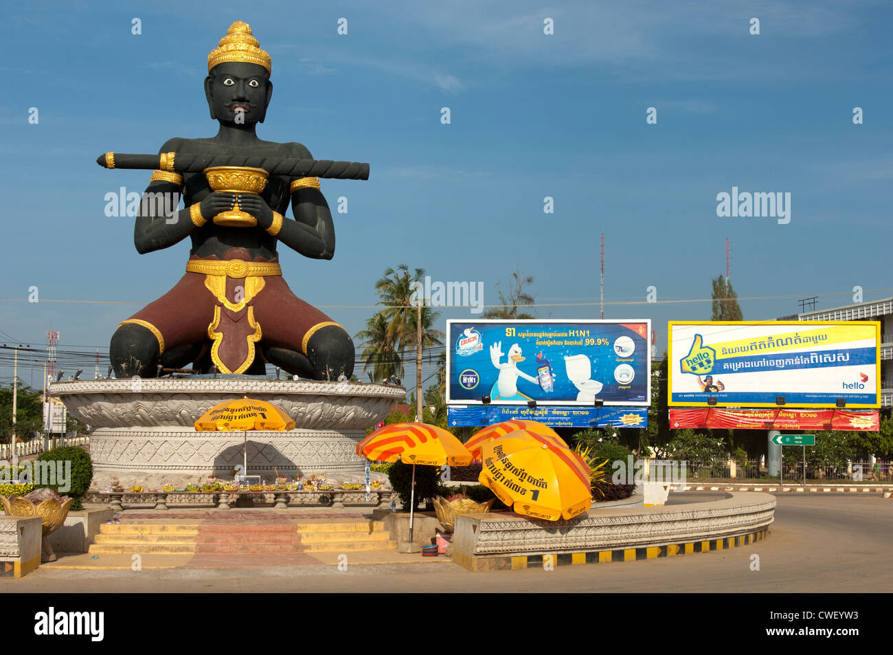 Statue of Ta Dambong (Black man) with his magic stick next to publicity posters, Battambang, Cambodia - Stock Image
